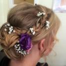 Hochzeitfrisur mit Perlen und Blumen